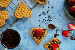 Belgian waffles in the shape of hearts with fresh strawberries and chocolate topping Stock Image