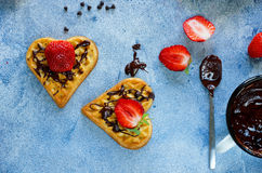 Belgian waffles in the shape of hearts with fresh strawberries and chocolate topping on blue table Royalty Free Stock Photography
