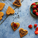 Belgian waffles in the shape of hearts with fresh strawberries and chocolate topping on blue table Royalty Free Stock Images