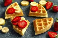 Belgian waffles with strawberries, banana and maple syrup. Belgian waffles with strawberries, banana and maple syrup close up royalty free stock photo