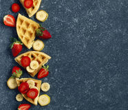 Belgian waffles with strawberries, banana and maple syrup. With copy space royalty free stock photos