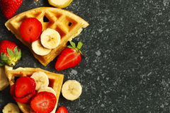 Belgian waffles with strawberries, banana and maple syrup. Belgian waffles with strawberries, banana and maple syrup on stone background with copy space royalty free stock photography