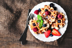 Belgian waffles with strawberries, blueberries and syrup on wood Royalty Free Stock Image