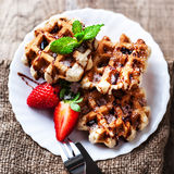 Belgian waffles with strawberries, mint, sugar powder and chocol Stock Photography