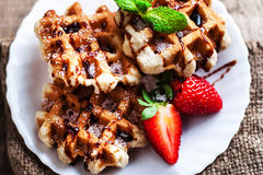 Belgian waffles with strawberries, mint, sugar powder and chocolate syrup on wooden background, image in rustic style with copy stock photo