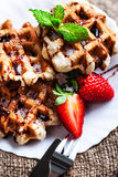 Belgian waffles with strawberries, mint, sugar powder and chocol Stock Photos