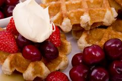 Belgian Waffles,  Summer Fruit and Drizzled Maple Syrup. A pile of Belgian Waffles and fresh summer fruits with maple syrup drizzled on Stock Images