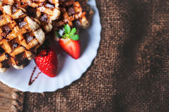 Belgian waffles topped with strawberries, syrup and icing. Homem. Ade breakfast in rustic style, toned image with copy space Royalty Free Stock Image