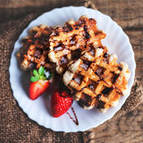 Belgian waffles topped with strawberries, syrup and icing. Homem Stock Image