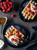 Belgian waffles with whipped cream and berries. Two plates of belgian waffles with whipped cream and raspberries on dark marble background. Top view Royalty Free Stock Images