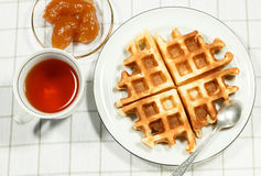 Belgian waffles on white plate. And cup of black tea with apple jam. Serving on the light-colored tablecloths Stock Photography