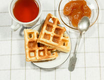 Belgian waffles on white plate and cup of black tea. With apple jam. Serving on the light-colored tablecloths Royalty Free Stock Images