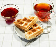 Belgian waffles on white plate. And cup of black tea with currant jam. Serving on the light-colored tablecloths Royalty Free Stock Images