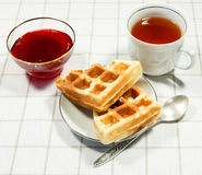 Belgian waffles on white plate and cup of black tea. With currant jam. Serving on the light-colored tablecloths Stock Photos