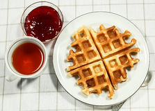 Belgian waffles on white plate. And cup of black tea with currant jam. Serving on the light-colored tablecloths Stock Photography