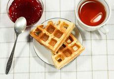 Belgian waffles on white plate. And cup of black tea with currant jam. Serving on the light-colored tablecloths Stock Image