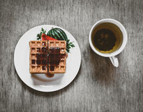 Belgian waffles on white plate and cup of black tea with currant jam. Royalty Free Stock Image