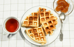 Belgian waffles on white plate and cup of tea. Belgian waffles on white plate and cup of black tea with currant jam. Serving on the light-colored tablecloths Stock Images