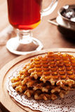 Belgian waffles on wooden table with glass of tea Royalty Free Stock Photos