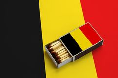 Belgien-Flagge wird in einer offenen Streichholzschachtel gezeigt, die mit Match gefüllt wird und auf einer großen Flagge liegt stockbild