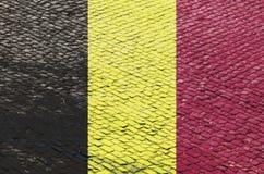 Belgische Flagge auf einem Kopfstein-Straßen-Muster lizenzfreies stockfoto
