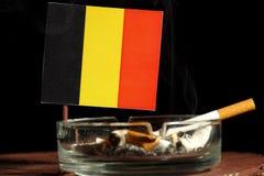 Belgische Flagge mit brennender Zigarette im Aschenbecher lokalisiert auf Schwarzem Lizenzfreies Stockbild