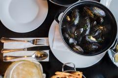 Belgische lunch: gestoomd mosselen, frieten en bier stock foto