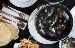 Belgische lunch: gestoomd mosselen, frieten en bier stock foto's