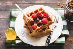 Belgische wafels met frambozen en honing stock fotografie