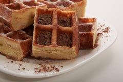 Belgische wafels met geraspt chocolade en suikerglazuur op een witte plaat Royalty-vrije Stock Foto