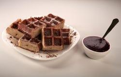 Belgische wafels met geraspt chocolade en suikerglazuur op een witte plaat Stock Fotografie