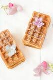 Belgische Waffeln, besprüht mit Zuckerglasur, rosa Blumen Lizenzfreies Stockbild