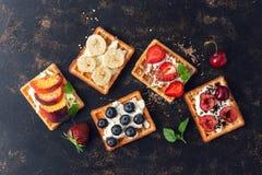 Belgische Waffeln mit Blaubeeren, Erdbeeren, Pfirsichen, Kirschen und Banane Selbst gemachte Waffeln auf einem dunklen rustikalen stockbild