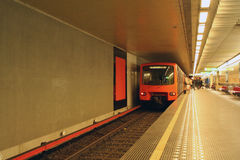 Belgium - Brussels - Orange subway underground aka metro train. Orange subway underground aka metro train standing on the station and blurred station decor and Royalty Free Stock Image