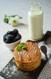 Belgium Dutch waffle cookies and caramel sauce with mint on wooden board and bottle of milk, bowl of blackberries and powdered stock image