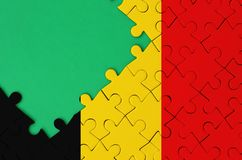 Belgium flag is depicted on a completed jigsaw puzzle with free green copy space on the left side.  stock image