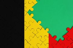 Belgium flag is depicted on a completed jigsaw puzzle with free green copy space on the right side.  vector illustration