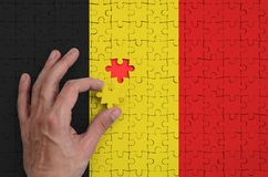 Belgium flag is depicted on a puzzle, which the man`s hand completes to fold.  stock images