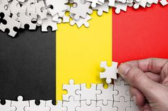 Belgium flag is depicted on a table on which the human hand folds a puzzle of white color.  royalty free stock photo