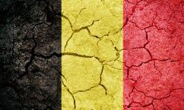 Kingdom of Belgium flag. Belgium flag on dry earth ground texture background stock photos