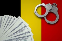 Belgium flag with handcuffs and a bundle of dollars. The concept of illegal banking operations in US currency.  stock photography