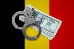 Belgium flag with handcuffs and a bundle of dollars. Currency corruption in the country. Financial crimes.  royalty free stock photo
