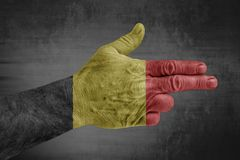 Belgium flag painted on male hand like a gun. Isolated on concrete background stock photos