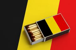 Belgium flag is shown in an open matchbox, which is filled with matches and lies on a large flag.  royalty free stock photo