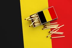 Belgium flag is shown on an open matchbox, from which several matches fall and lies on a large flag.  stock photos