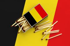 Belgium flag is shown on an open matchbox, from which several matches fall and lies on a large flag.  stock images