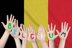 Belgium inscription on the children`s hands against the background of a waving flag of the Belgium.  royalty free stock photos