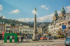 Belgium - Malmedy. Overview of the historic houses, and monument on the central square of Malmedy, Place Albert, Belgium, with a blue cloudy sky Royalty Free Stock Image