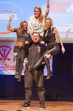 Belgium strongman Jimmy Laureys lifts girls on stage Royalty Free Stock Image
