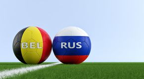 Belgium vs. Russia Soccer Match - Soccer balls in Belgium and Russia national colors on a soccer field. Copy space on the right side - 3D rendering Stock Image